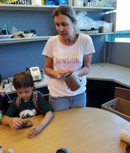 Auntie Nicole and her helper show the rocks from the department's collection.