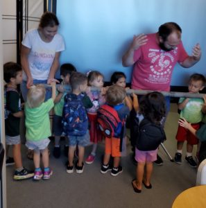 The preschoolers, Auntie Nicole, and Uncle Colin hold a drill core that extends over five feet!