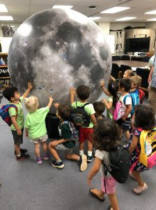 At the Pacific Regional Planetary Data Center, the preschoolers play with the inflatable moon.