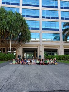 The preschoolers sit outside of the POST building.